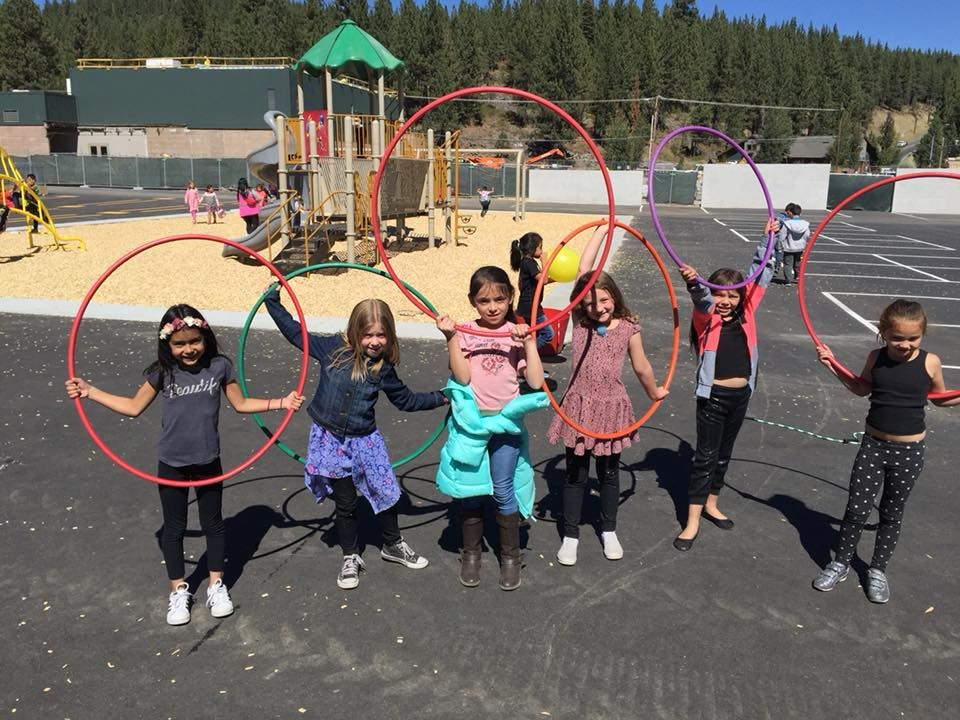 Young students on playground with hula hoops