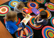 This is a colorful photo of kids reading on the carpet as reading buddies