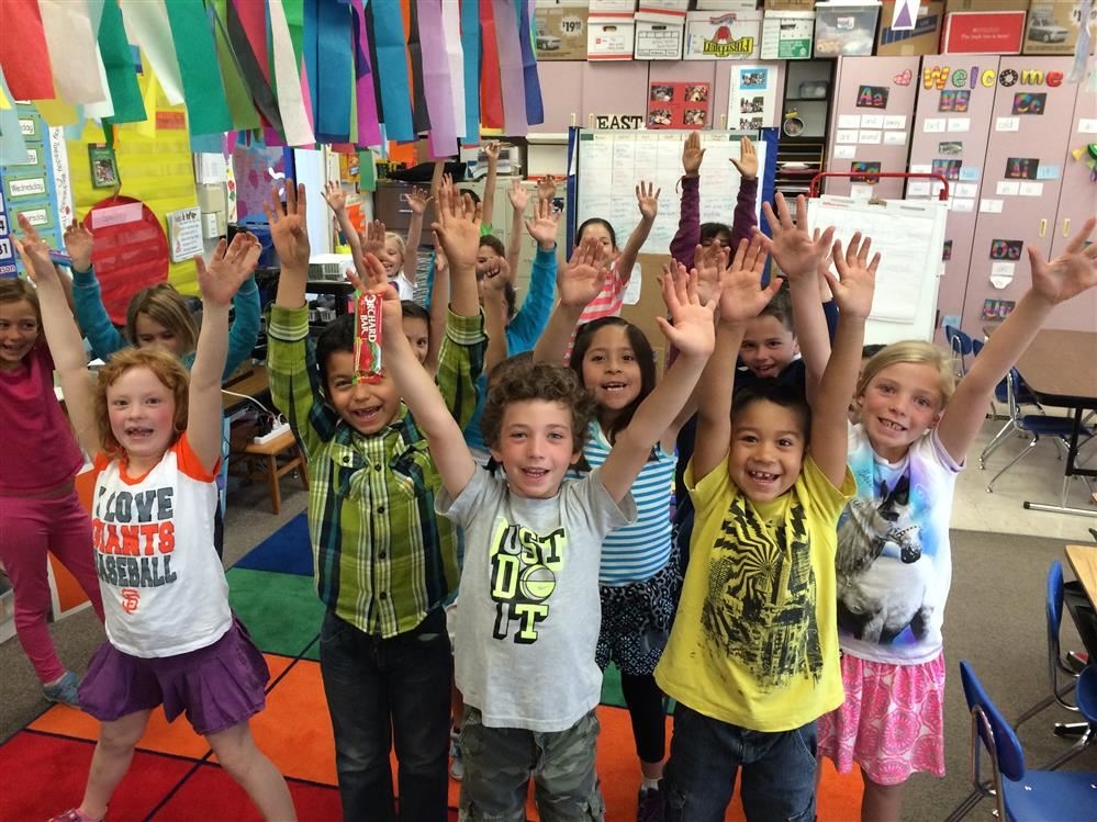PIcture of kindergarten class with hands up in the air